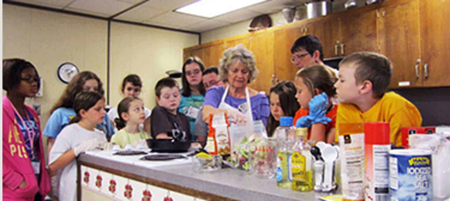 Teacher showing kids how to cook